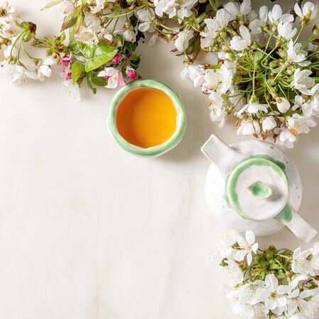 Craft handmade ceramic teapot and cup with hot tea decorated by spring blossom cherry branches over white marble background. Flat lay, space