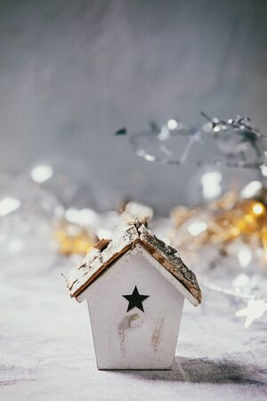 Christmas toy birdhouse and lightning garlands over old white wooden background. Christmas and New year decorations or greeting card. Copy space
