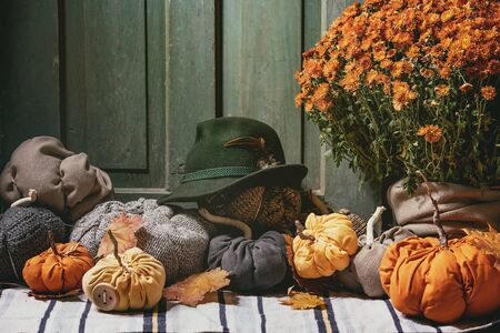 Wool and textile pumpkins for Halloween or Thanksgiving holidays home decor with autumn leaves, felt hat, pot of chrysanthemums flowers on knitted doormat with old wooden door at background.