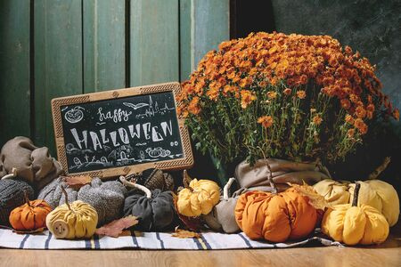 Wool and textile pumpkins for Halloween holidays home decor with autumn leaves, black chalkboard with Happy Halloween lettering, pot of flowers on knitted doormat with old wooden door at background.
