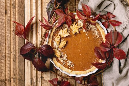 Traditional homemade autumn pumpkin pie for Thanksgiving or Halloween dinner served in ceramic dish with red autumn leaves over wooden plank background. Flat lay, space