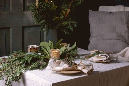 Christmas or New year table setting with empty ceramic plates, napkins, Christmas thuja wreath, luminous garland and burning candles on white tablecloth. Chair with plaid and pillow. Holiday mood