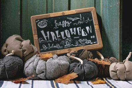 Wool and textile pumpkins for Halloween holidays home decor with autumn leaves, black chalkboard with Happy Halloween lettering on knitted doormat with old wooden door at background.