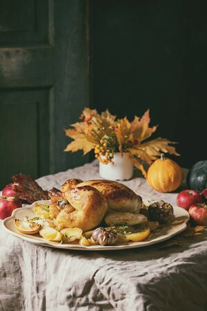Thanksgiving or Halloween dinner with baked chicken with potatoes and lemons on big ceramic dish, yellow autumn leaves and pumpkins as decorations over linen table cloth. Rustic style