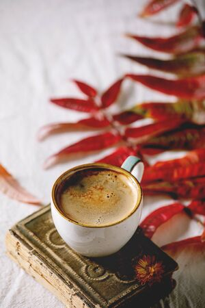 Cup of black coffee espresso standing on white cloth with autumn leaves and flowers, old books.