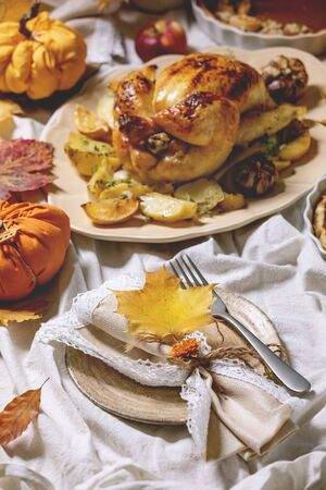 Thanksgiving or Halloween dinner with baked chicken with potatoes and lemons on big ceramic dish, pumpkin pies, plates, yellow autumn leaves and pumpkins as decorations over white table cloth.
