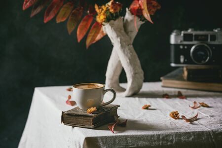 Cup of black coffee espresso standing on white table cloth in dark room with autumn leaves and flowers in clay vase, old books, vintage camera. 스톡 콘텐츠