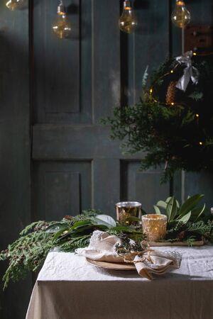 Ajuste de la tabla de Navidad o año nuevo con platos de cerámica vacíos, servilletas, corona de thuja de Navidad, guirnalda luminosa y velas encendidas sobre mantel blanco. Ánimo de vacaciones