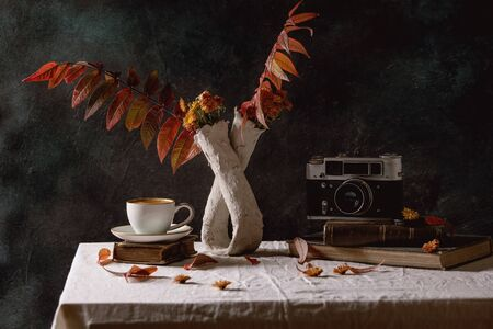 Cup of black coffee espresso standing on white table cloth in dark room with autumn leaves and flowers in clay vase, old books, vintage camera. Banco de Imagens