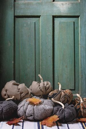 Wool and textile pumpkins for Halloween or Thanksgiving holidays home decor with autumn leaves on knitted doormat with old wooden door at background.