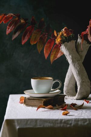 Cup of black coffee espresso standing on white table cloth in dark room with autumn leaves and flowers in clay vase, old books.