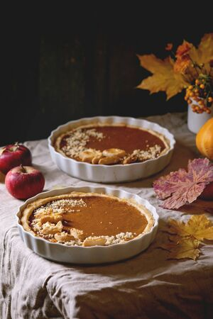 Traditional homemade autumn pumpkin pies for Thanksgiving or Halloween dinner served in ceramic dish with yellow autumn leaves, pumpkins and apples on linen table cloth. Dark rustic style Stock Photo