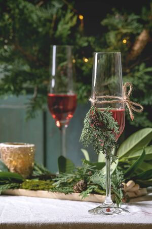 Christmas or New year table setting with two glasses red sparkling wine, plates, napkins, Christmas thuja wreath, luminous garland and burning candles on white tablecloth. Holiday mood