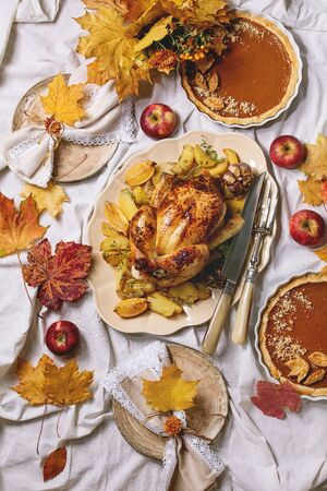 Thanksgiving or Halloween dinner with baked chicken with potatoes and lemons on big ceramic dish, pumpkin pies, plates, yellow autumn leaves, pumpkins as decorations over white table cloth. Flat lay