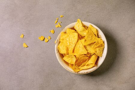 Tortilla nachos corn chips in ceramic bowl over brown texture background. Flat lay, space