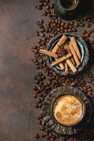 Black coffee espresso with foam in black ceramic cup, with saucer, cezve coffee pot, spices and roasted beans above over brown texture background. Flat lay, copy space