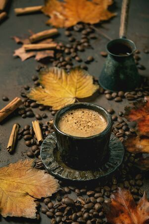 Black coffee espresso with foam in black ceramic cup, with saucer, cezve coffee pot, autumn leaves, spices and roasted beans above over brown texture background.