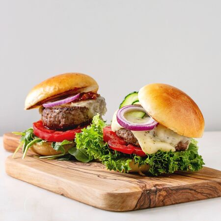 Two homemade fast food burgers classic hamburger or cheeseburger with beef, salad, cheese and tomato served on wooden cutting board on white marble kitchen table. Copy space. 写真素材