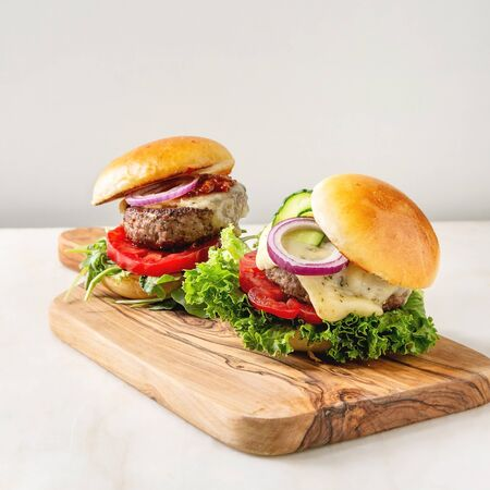 Homemade fast food burger classic hamburger or cheeseburger with beef, salad, cheese and tomato served on ceramic plate on white marble kitchen table. Copy space. 写真素材