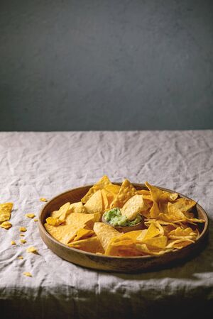 Tortilla nachos corn chips with avocado guacamole sauce served in wood plate on linen table cloth. Mexican snack