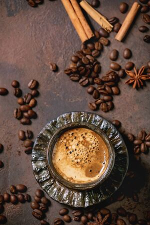 Black coffee espresso with foam in black ceramic cup, with saucer, spices and roasted beans above over brown texture background. Flat lay, space 写真素材