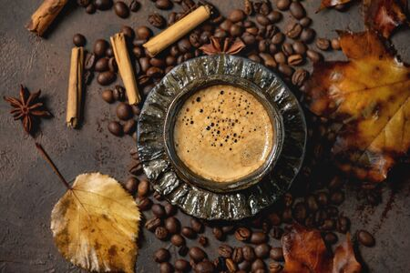 Black coffee espresso with foam in black ceramic cup, with saucer, autumn leaves, spices and roasted beans above over brown texture background. Flat lay 写真素材
