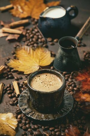 Black coffee espresso with foam in black ceramic cup, with saucer, cezve coffee pot, autumn leaves, spices, jug of cream and roasted beans above over brown texture background.