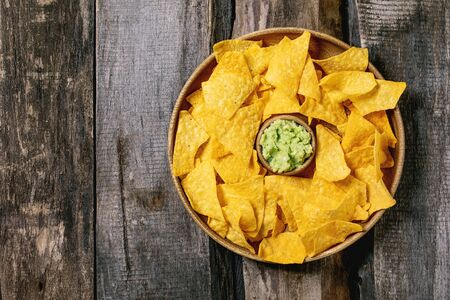 Tortilla nachos corn chips with avocado guacamole sauce served in wood plate over old wooden background. Flat lay, space