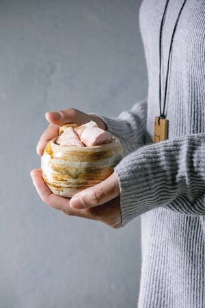 Woman in grey sweater hold in hands ceramic mug with hot chocolate or cocoa with marshmallow. 写真素材