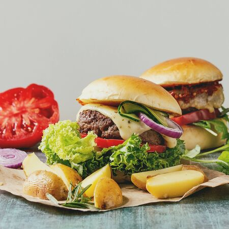 Two Homemade fast food burgers classic hamburger or cheeseburger with beef, salad, cheese and tomato served on paper with baked country potatoes on blue texture table. Copy space.