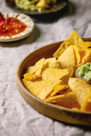 Tortilla nachos corn chips with avocado guacamole and tomato sauce served in wood plate on linen table cloth. Mexican snack, close up