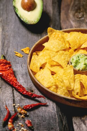 Tortilla nachos corn chips with avocado guacamole sauce served in wood plate with half of avocado and chilli peppers over old wooden background.