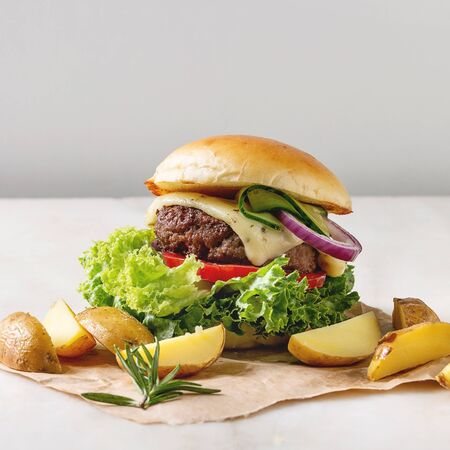 Homemade fast food burger classic hamburger or cheeseburger with beef, salad, cheese and tomato served on paper with baked country potatoes on white marble kitchen table. Copy space.