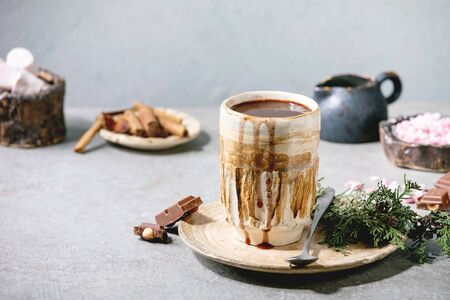 Hot chocolate or cocoa served in ceramic mug with saucer, marshmallow, cinnamon sticks, chopped chocolate, pink sugar and jug of cream on grey table.