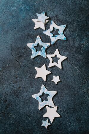 Christmas decoration ceramic stars white and blue glazed, different size, over blue texture background. Christmas and New year greeting card. Flat lay, space.