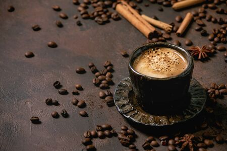 Black coffee espresso with foam in black ceramic cup, with saucer, spices and roasted beans above over brown texture background.