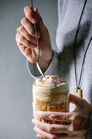 Woman in grey sweater hold in hands ceramic mug with hot chocolate or cocoa with marshmallow and spoon.
