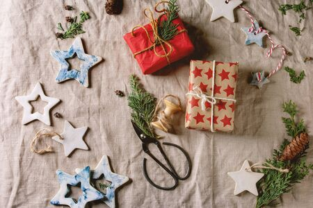 Christmas decoration ceramic stars white and blue glazed, different size, gift boxes in craft paper, green branches over linen cloth as background. Christmas, New year gift wrapping. Flat lay, space. 写真素材
