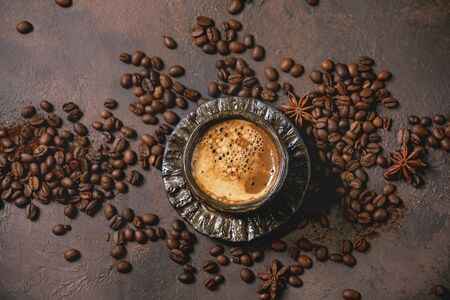 Black coffee espresso with foam in black ceramic cup, with saucer and roasted beans above over brown texture background. Flat lay, space 写真素材