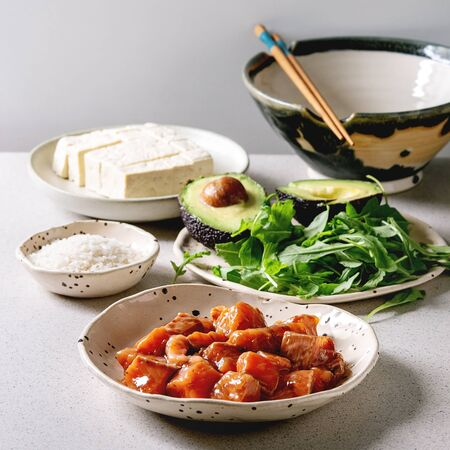 Ingredients for cooking poke bowl. Rice, soy sauce marinated salmon, avocado, tofu cheese and green salad in ceramic bowls served with wooden chopsticks over grey spotted table.