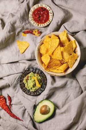 Tortilla nachos corn chips with avocado guacamole and tomato sauce served in ceramic bowl with half of avocado and chilli peppers over linen folded cloth as background. Flat lay, space