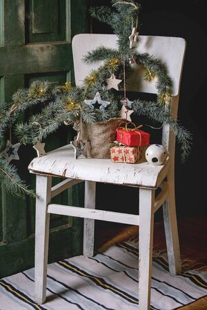 Christmas decoration fir tree branches, ceramic stars, luminous garland, gift boxes in craft paper on vintage white chair with wooden door at background. Christmas and New year interior.