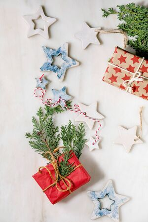 Christmas decoration ceramic stars white and blue glazed, different size, gift boxes in craft paper, green branches over white marble background. Christmas and New year greeting card. Flat lay, space. 写真素材
