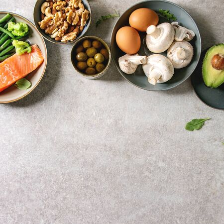 Ketogenic diet ingredients for cooking dinner. Raw salmon, avocado, broccoli, bean, olives, nuts mushrooms, eggs in ceramic bowls. Grey texture background. Flat lay, copy space