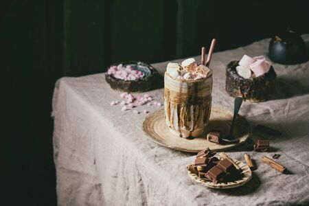 Hot chocolate or cocoa with marshmallow served in ceramic mug with saucer, cinnamon sticks, chopped chocolate, pink sugar and jug of cream on grey table cloth. Rustic style