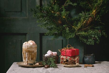 Hot chocolate or cocoa with marshmallow served in ceramic mug with saucer, cinnamon sticks, chopped chocolate, pink sugar and Christmas gifts on grey table cloth. Christmas mood