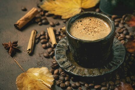 Black coffee espresso with foam in black ceramic cup, with saucer, autumn leaves, spices and roasted beans above over brown texture background.