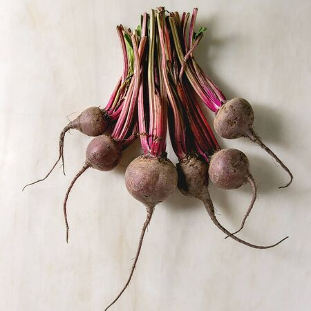 Bundle of young organic garden beetroot over white marble background. Flat lay, space