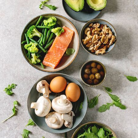 Ketogenic diet ingredients for cooking dinner. Raw salmon, avocado, broccoli, bean, olives, nuts mushrooms, eggs in ceramic bowls. Grey texture background. Flat lay, space 写真素材