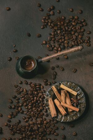 Black turkish coffee with foam in old vintage cezve coffee pot, cinnamon sticks in ceramic saucer and roasted beans above over brown texture background. Flat lay, space 写真素材